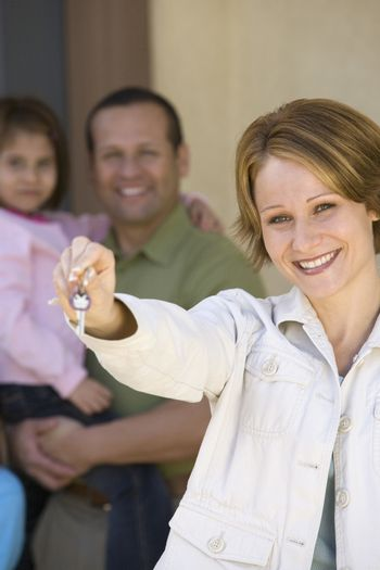 Portrait of happy woman holding new home key with family in background