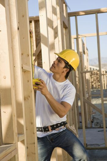 Construction worker measuring timber at the site