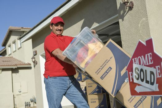 Happy mature man delivering cardboard boxes into a new house