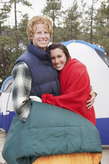 Portrait of happy Caucasian couple embracing in front of campaign tent