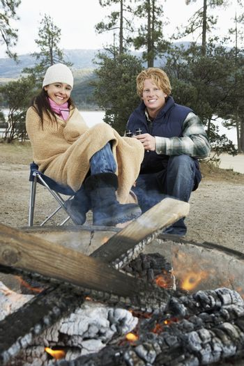 Portrait of young couple sitting by bonfire spending time together