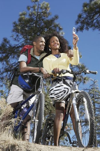 Young African American couple self photographing on bicycle