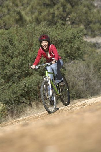 Young Asian female riding bicycle on dirt road