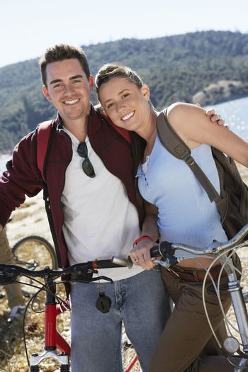 Portrait of Caucasian couple standing together by bicycle