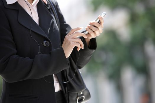 Mid section of business woman dialing on cell phone