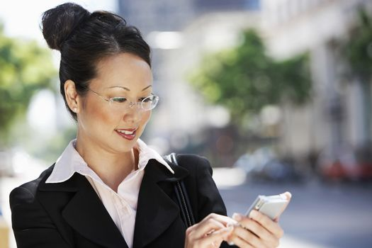 Happy Japanese business woman text messaging