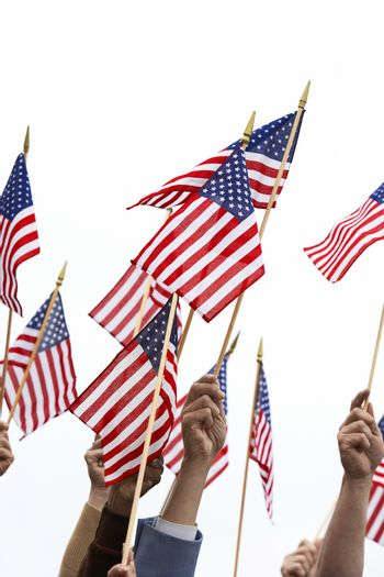 Hands holding American flag over white background