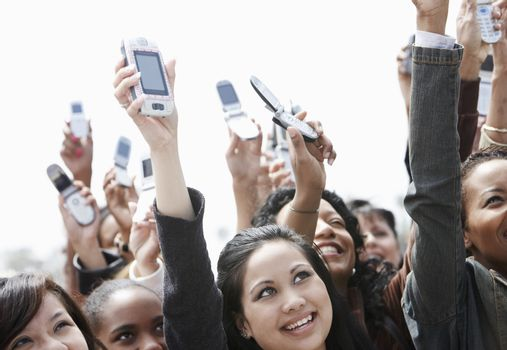 Crowd holding up cell phones head and shoulders
