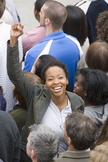 Woman with arm raised in crowd