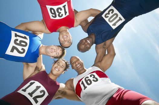 Track and field athletics smiling in a circle view from below