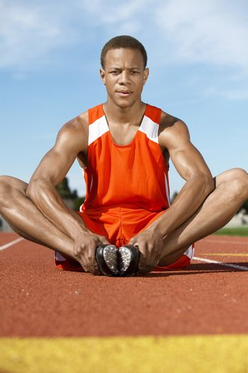 Young male athlete warming up on racing track