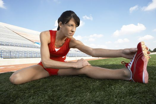 Young female athlete stretching on the field
