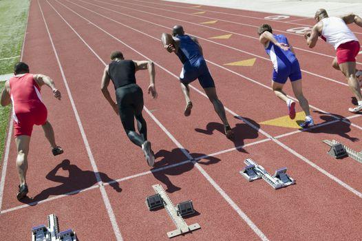 Male sprinters leaving starting blocks