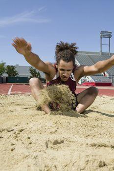 Male long jumper landing in sand pit