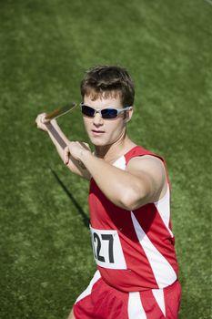 Male Caucasian athlete throwing javelin