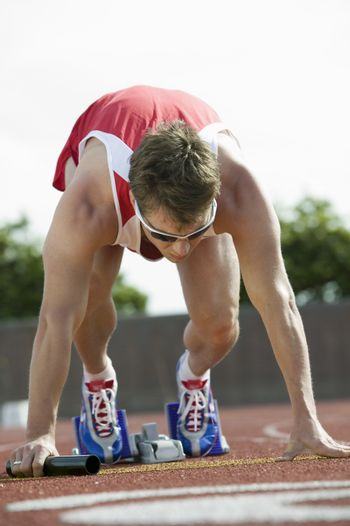 Male athlete in starting blocks with baton
