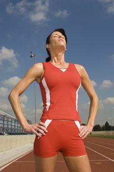 Female athlete with eyes closed in stadium