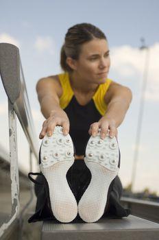 Female Caucasian athlete warming up on stadium bench