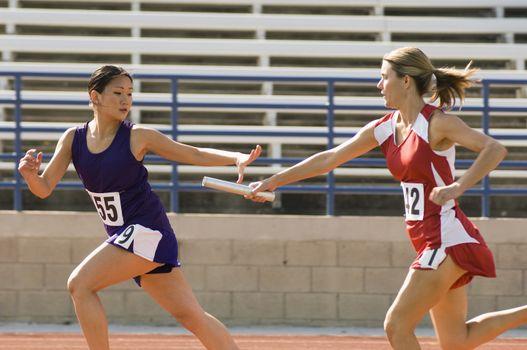 Female runners passing baton in relay race