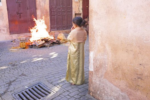 FES, MAROCCO - October 15 : Girl watching the fire on Eid al-Adha, October 15, 2013. The festival is celebrated by sacrificing a lamb or other animal and distributing the meat to relatives, friends, and the poor.