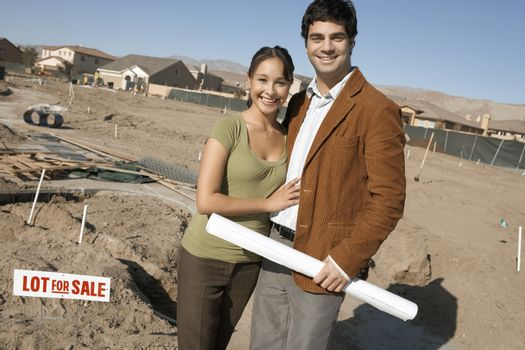 Portrait of man holding blueprint while standing with woman at an under construction plot