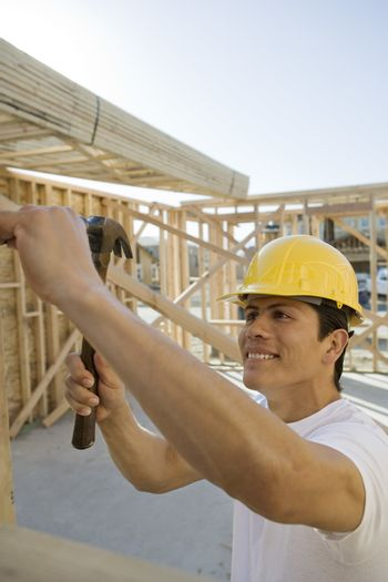 Middle aged construction worker hammering at construction site