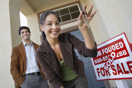 Happy couple with keys to new home by sold signboard