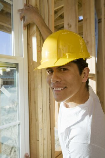 Portrait of middle aged manual worker installing window of a house