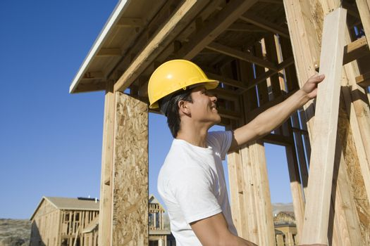 Construction worker holding a wooden beam at construction site