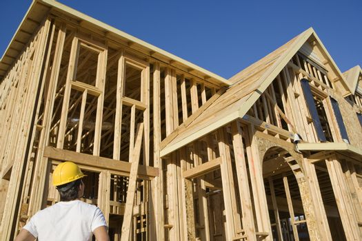Rear view of construction worker looking at an unfinished residential housing frame