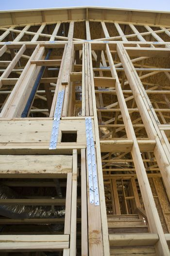 Low angle view of incomplete residential home framing under construction