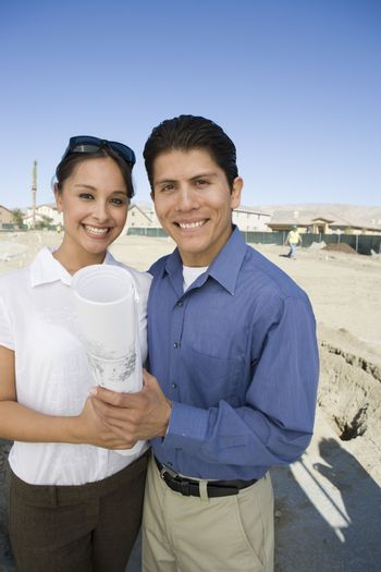 Portrait of a happy Hispanic Latin couple with blueprint at an under construction plot