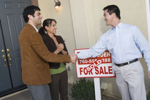 Happy couple shaking hands with estate agent in front of their new home