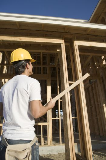 Rear view of construction worker holding wooden beam at construction site