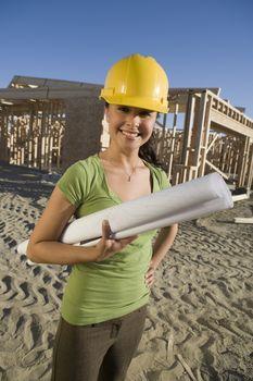 Portrait of happy Hispanic female architect holding blueprint with construction framework in background