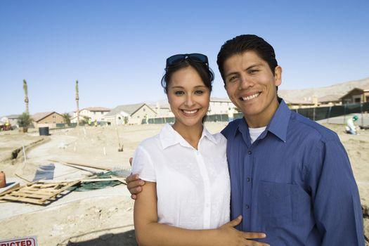 Portrait of happy Hispanic couple standing arm around at construction site