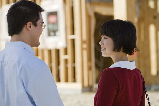 Mature Chinese couple at a construction site with unfinished housing frame in background