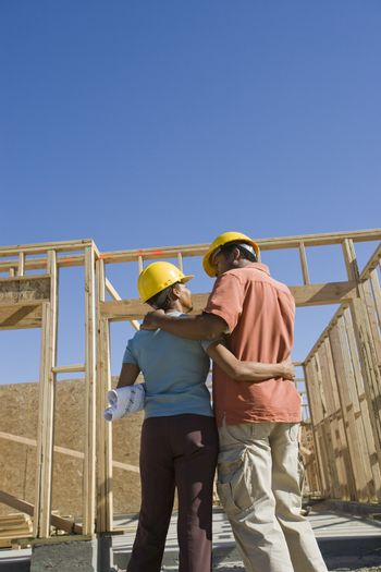 Rear view of an African American couple standing in front of an unfinished housing construction