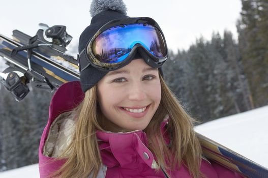 Teenage girl (16-17) holding skis in snow portrait.