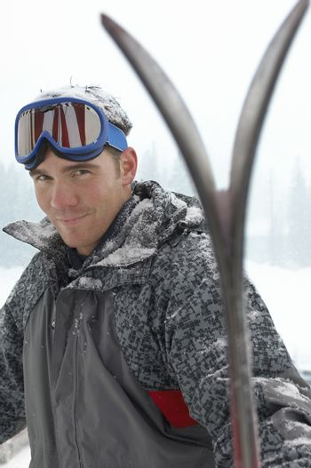 Portrait of a young man wearing ski goggles on head with skis in snow