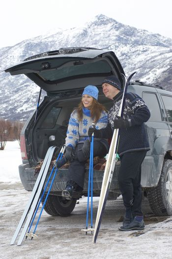 Happy couple relaxing at the back of a vehicle with cross country skis and poles in snow