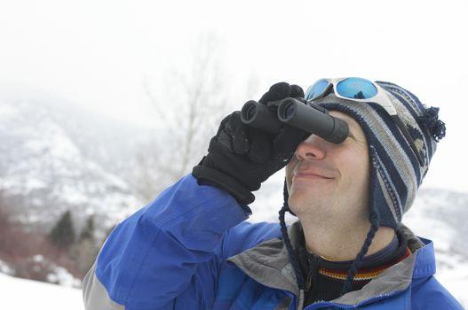 Man looking through binoculars in snow covered field head and shoulders