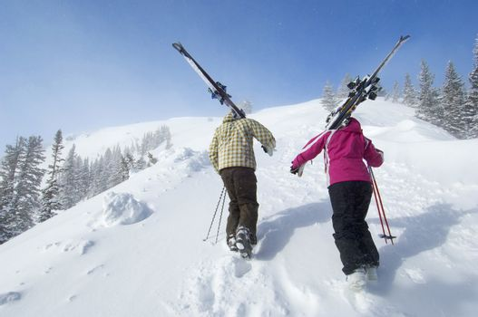 Rear view of a couple with skis hiking up the snow slope