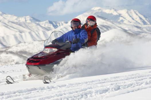 Multiethnic couple riding motor sledge on snow