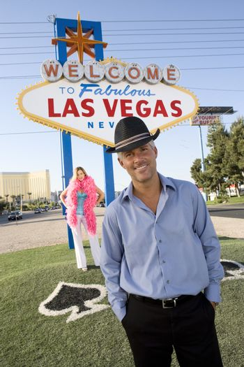 Portrait of a confident mature man with woman and Las Vegas sign in the background