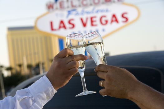 Hands toasting white wine with car and signboard in the background