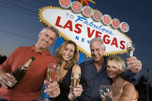 Portrait of happy friends with champagne against 'Welcome to Las Vegas' sign