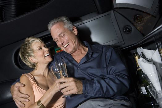Happy mature couple toasting champagne sitting in limousine and toasting