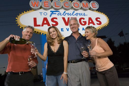 Low angle view of friends with champagne against 'Welcome to Las Vegas' sign