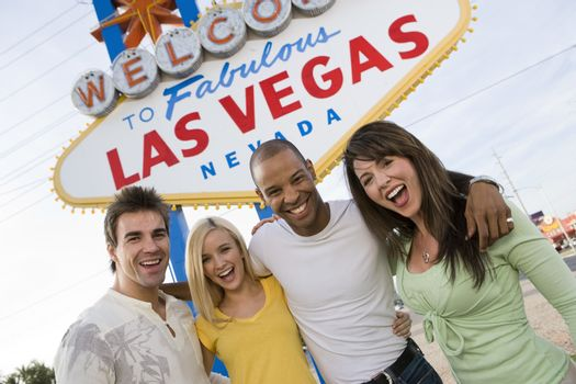 Portrait of happy friends standing together against 'Welcome To Las Vegas' sign